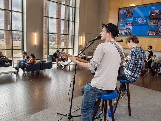 As MTSU visitors await the start of the campus tour, musicians Kenny Arnold, left, and Cooper Gilliam entertain from the stage.  Gilliam is a freshman from Martin, Tenn., while Arnold is a sophomore from Baltimore, Md. Both are commercial songwriting majors.