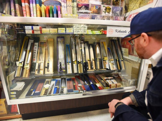 Chris Arturo, Chef at Ani Ramen House in Montclair looks at Japanese kitchen knives at Mitsuwa Marketplace in Edgewater.