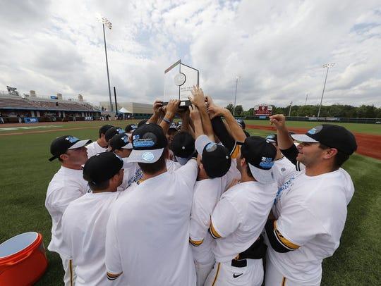 Iowa players hoist the Big Ten Tournament trophy after