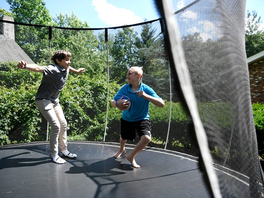 Bennett, right, plays on the trampoline with his brothers Aidan, left, and Max (not pictured) in their backyard. When Bennett, 10, was diagnosed with non-Hodgkin's lymphoma in February, his brothers decided to raise money to buy him gifts to lift his spirits. But $30,000 dollars later, they decided to donate it to Tackle Kids Cancer fund at HackensackUMC.