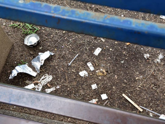 Used needles and other signs of drug use under a bench at Barbour Park in Paterson.