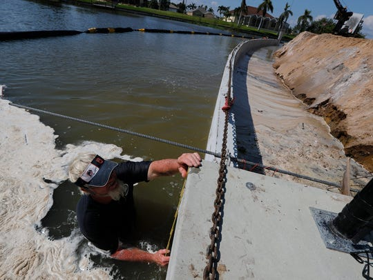 Jason Brown checks the leveling of a seawall under