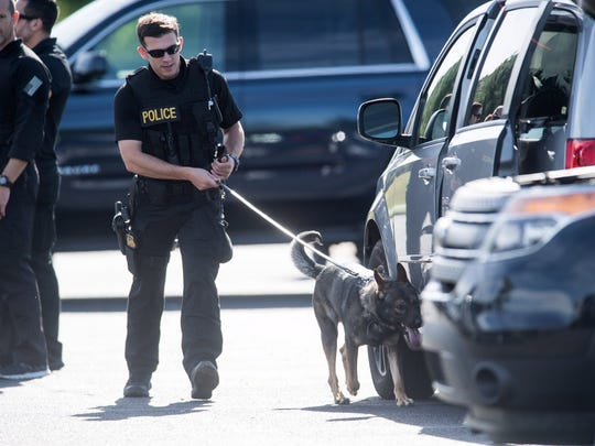 Bomb-sniffing dogs check vehicles parked at Greenville-Spartanburg International Airport ahead of President Donald Trump's visit to Greenville on Monday, Oct. 16, 2017.