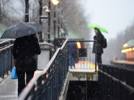 Commuters wait in rain and snow in April 2016 at the