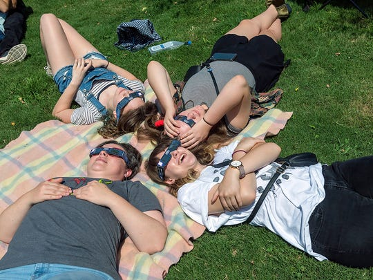 Lying on a blanket, a group of four people wearing