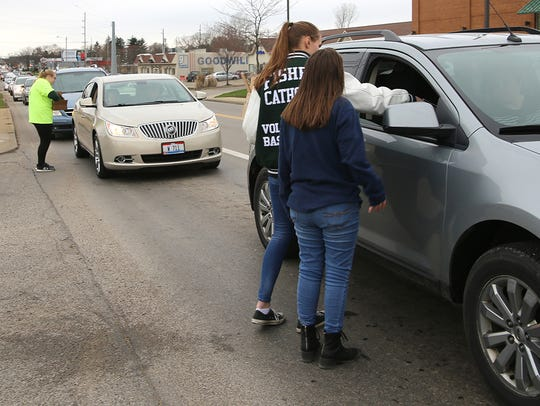 Fisher Catholic Interact Club members hand out flyers