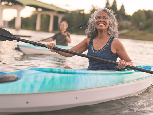 An ethnic senior woman smiles while kayaking with her husband