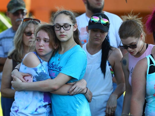 People wait for the start of a vigil in Santa Fe, Texas