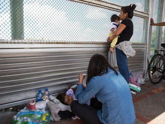 Two Guatemalan women seeking asylum wait  Wednesday, June 27, 2018 on the Mexican side of the international bridge to Brownsville, Texas.