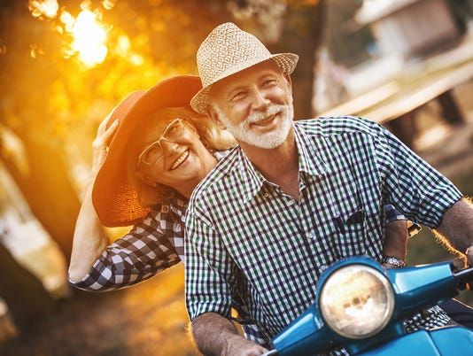 Senior couple on a scooter bike driving through city streets.