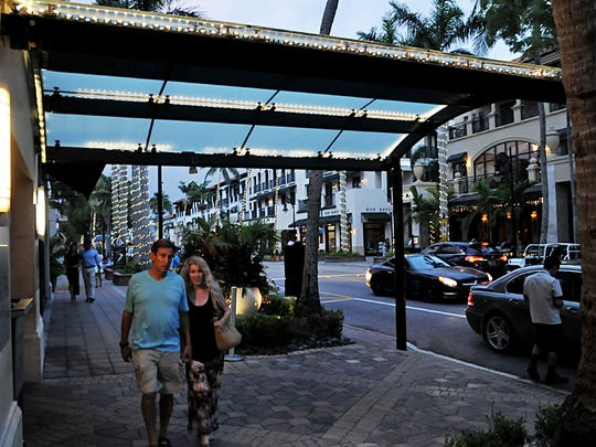 A couple strolls under the canopy of The Inn on 5th at 699 Fifth Avenue South in Naples on June 15, 2018.