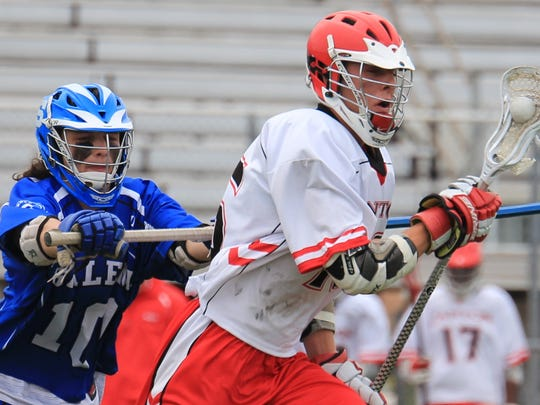 Salem's Andy Gregor (left) tries to check Canton's Nolan Gilo during Saturday's varsity boys lacrosse match.