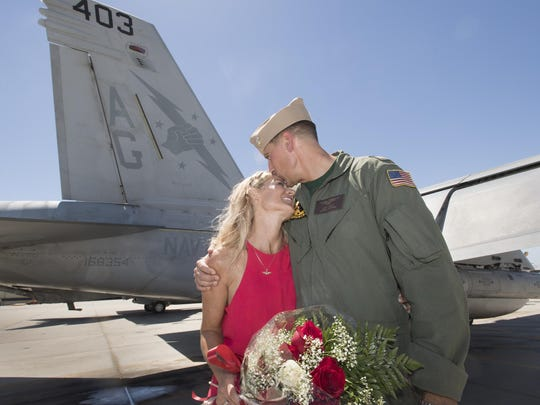 Lt. Commander John Hiltz and girlfriend Mary Strecker share a moment after Hiltz made a surprise proposal to her as Naval Air Station Lemoore welcomed home Strike Fighter Squadron VFA-25's Fist of the Fleet pilots and crew on Tuesday, July 12, 2016. The group was deployed in November of 2015 with the Harry S. Truman Carrier Strike Group.