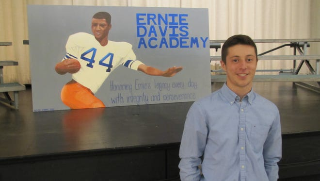 Elmira High School senior Kevin Strong is shown with the four-foot by six-foot mural of Ernie Davis that he painted and presented Friday to Ernie Davis Academy in Elmira.