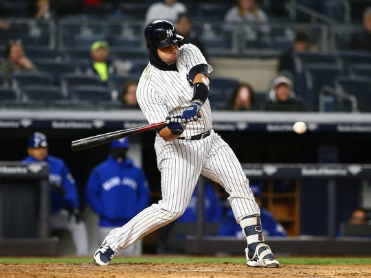 Apr 20, 2018; Bronx, NY, USA; New York Yankees right fielder Giancarlo Stanton (27) hits a two run home run against the Toronto Blue Jays during the third inning at Yankee Stadium.