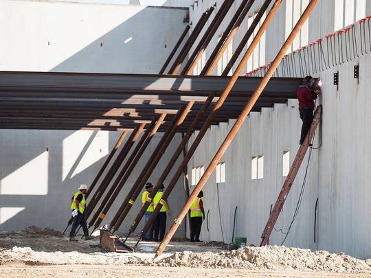 Workers are seen during construction of the new high school in Bonita Springs, Fla., on Thursday, June 29, 2017.