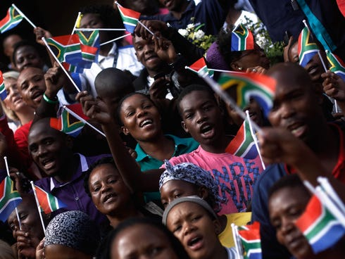 People react as procession for former South African president Nelson Mandela had makes its way through the streets of Pretoria, South Africa, on Dec. 11, 2013.