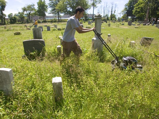 A volunteer mows the overgrown grass at Mt. Zion Cemetery near Wilmington in 2008.