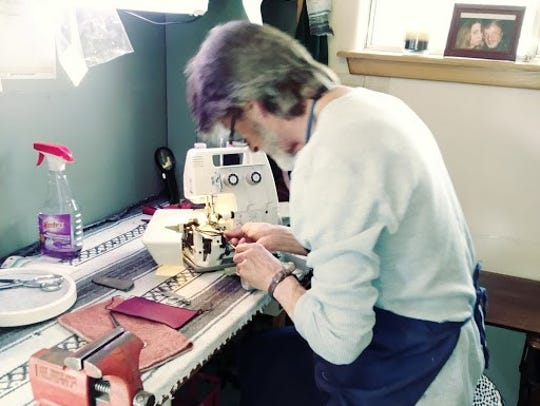 Don Vick works on a sewing machne at the business.