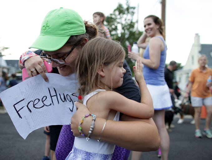 Marianna Oppman gives out free hugs as local residents