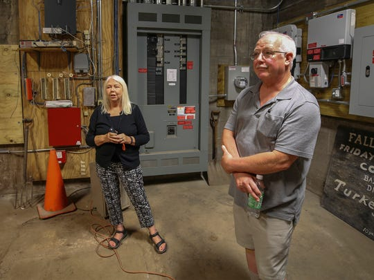 Trisha Tull, with the Green Team at First Presbyterian Church, left and Rick Lovett, right, talk about the Solarize the Brightside initiative.  They are in the original coal room at the church that now host control panels for the church's solar panels.