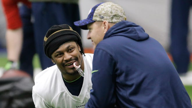 Seattle Seahawks running back Marshawn Lynch holds a candy cane in his mouth as he talks with offensive coordinator Darrell Bevell, right, before NFL football practice, Wednesday, Jan. 6, 2016, in Renton, Wash. Lynch has been recovering since having abdominal surgery last November.