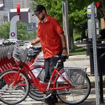 Hayden Stone, a field technician, places a bike in a rack at one of several Covington locations after their June opening.