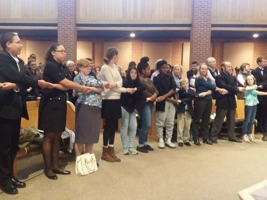 "Local residents gathered for the annual Martin Luther King Jr. service Sunday joined hands to sing ""We Shall Overcome"" in honor of the martyered civil rights leader"