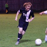 Calvary's Reed Mathews (24) competes against St. Frederick midfielder John Ellender (7) during Thursday's playoff game.