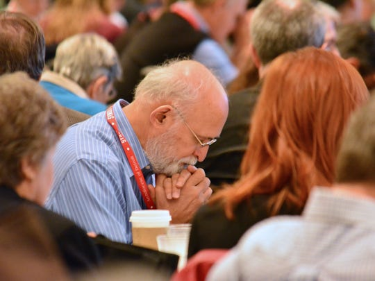 Synod members pray before the large group session on