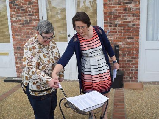 Carol Anne Hayes (left), who is developmentally disabled, burns her mortgage note Thursday with the help of Carolyn Gresham, program supervisor for the waiver program at Evergreen Life Services. Hayes got her house through Habitat for Humanity in 2000.