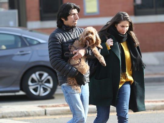 Hans Duenas holds Winnie as he walks with Lori Mancini,