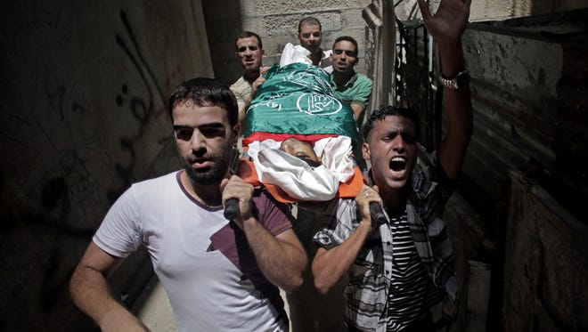 Palestinian relatives of Mohammed Naser chant slogans as they carry his lifeless body to the family house during his funeral in the Khan Younis refugee camp in the southern Gaza Strip on July 19, 2014.