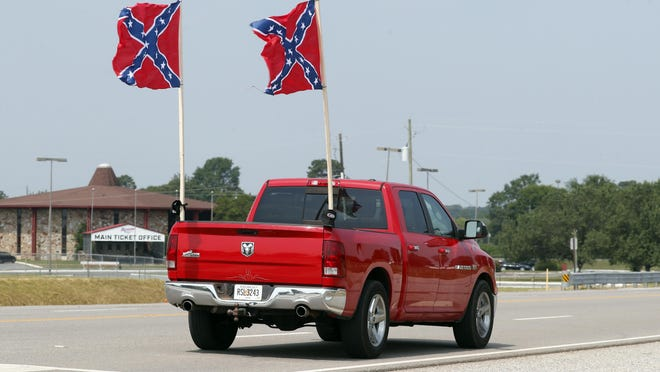 A truck flying confederate flags passes the main entrance to Talladega Superspeedway Sunday, June 21, 2020, in Talladega, Ala.