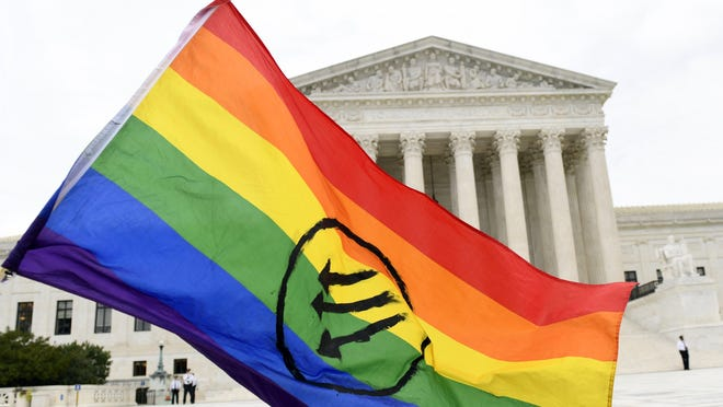 Protesters gather outside the Supreme Court in Washington, Tuesday, Oct. 8, 2019, where the Supreme Court heard arguments on whether a 1964 civil rights law prevents the firing of workers who are LGBT and transgender.