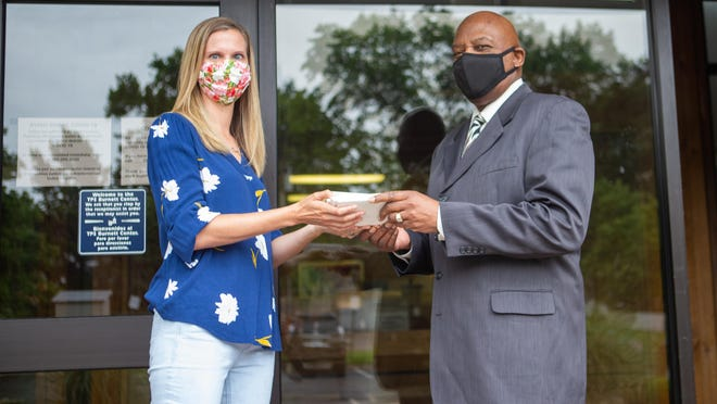 Larry Robbins, right, Topeka USD 501 deputy superintendent of operations, holds a stack of gift cards Tuesday with Jamie Stafford, Topeka South Rotary Sole Mates chair, outside the Burnett Center at 624 S.W. 24th St. The usual distribution of shoes was changed to gift cards this year to offer students the ability to buy school supplies.