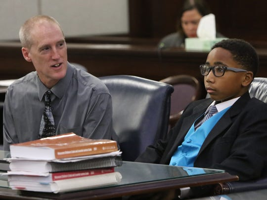 Isaiah (right) and Dan O'Brien testify before Judge Lloyd Carter during the final adoption proceedings for Isaiah and his twin brothers Mikey and Malachi by Dan and Lori O'Brien of Brookfield.
