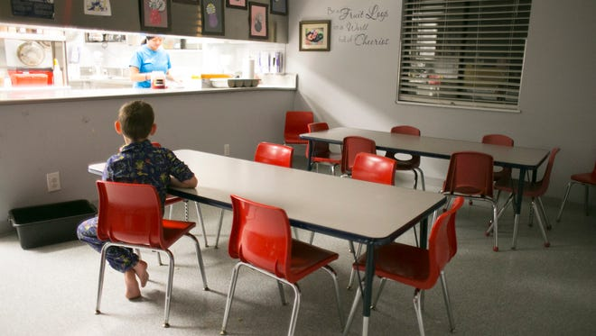 An 8-year-old boy sits alone in the kitchen waiting for a snack at Child Crisis Arizona on January 28, 2016. The shelter houses nearly 30 children ages zero through eight, who are primarily brought in from the Department of Child Services. The children stay at the shelter an average of six to nine months.