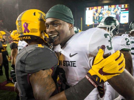 Michigan State running back LJ Scott hugs Minnesota