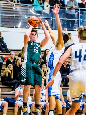 Cole Kleiver, 23, of Williamston knocks down a 3-point shot over a Lansing Catholic defender during its game Friday, December 9, 2016, in Lansing.