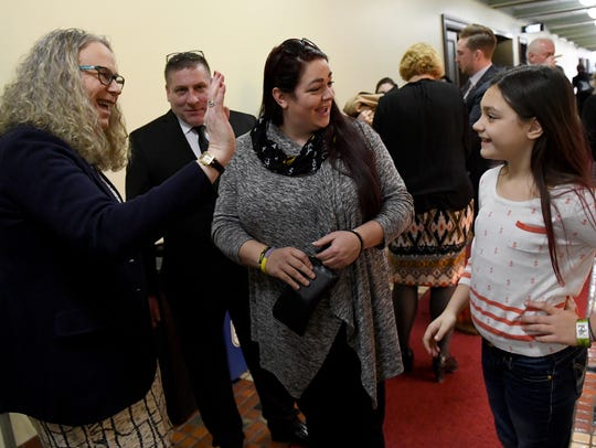 Bill Kohler, second from left, and Sara Weinhold, look on as Dr. Rachel Levine, left, with the Pennsylvania Department of Health, high fives Weinhold's 9-year-old daughter, Noelle, in the hallways of the Capitol building in Harrisburg. Kohler and the Weinholds were advocating for more funding for pediatric cancer research.