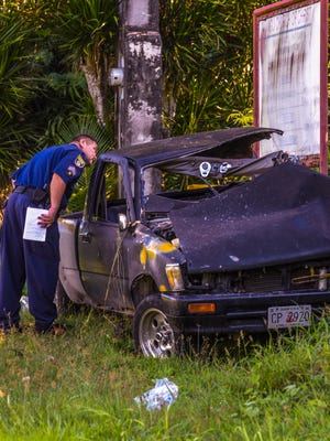 Guam Police Department officers conduct an investigation of a fatal crash, involving a Toyota Hilux pickup truck, that occurred near the Yigo Church of Christ on Route 15 on Thursday, Nov. 23, 2017.