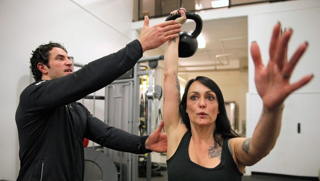 Daphne Morrissey does exercises with a twenty five pound kettlebell under the supervision of Brian Hahn, senior health and wellness director at the Carlson MetroCenter YMCA. These exercises help release tightness in the chest and abdominal muscles to aid in better posture.