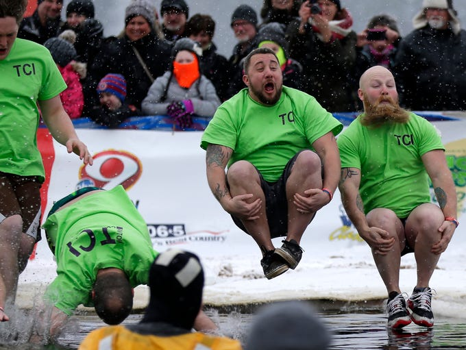 A team jumps into the river during the Polar Plunge,
