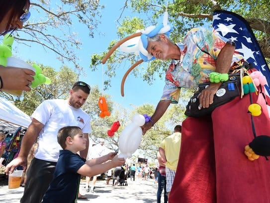 """Jeff """"The Balloon Guy"""" Dorian hands Michael Campion Jr., 4, of Port St. Lucie, a custom balloon character March 18, 2017, during the annual Taste of the Sea & Sandy Shoes Seafood Festival at Veterans Memorial Park in downtown Fort Pierce. Fort Pierce was named one of the most charming small towns in Florida by Touropia."""