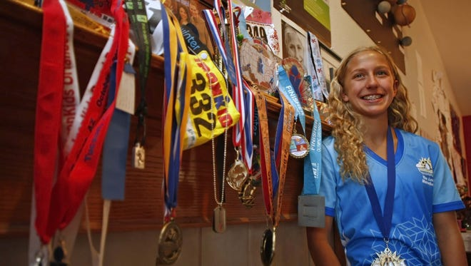 Winter poses with some of the awards she has accrued in a life of athletic endeavors. She plans to run a marathon on all seven continents before she turns 15 on Dec. 18. She already has completed three of the seven races needed to reach her goal. TIMOTHY J. GONZALEZ / Statesman Journal Winter Vinecki is a 14-year-old athlete who has participated in triathlons since she was five years old. Winter's father passed away in 2009 of prostate cancer, and Winter created a non-profit called Team Winter to raise money for prostate cancer awareness and research. Winter's family lives in Salem, and Winter lives in Park City Utah to train for aerial skiing in the 2018 winter Olympics. She has now set the record for youngest person to complete a marathon in Antarctica, and her newest goal is to run a marathon on every continent before she turns 15 in December. She's completed three of the seven marathons and so far has run in Antarctica, Africa, and North America.Photographed at her South Salem home on Monday, April 15, 2013.