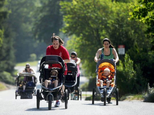"From left, Michelle D'Ettorre of York Township, Angela Hummel of Springettsbury Township, Miranda Kopp of Dallastown, and Stephanie Schuessler of Dallastown push their children up a steep hill in Spring Garden Township while training for a 5K last month. D'Ettorre, a personal trainer with York JCC, led a 6-week training program for moms running with strollers, culminating in a 5K race in Dover. ""Instead of taking her to the gym and dropping her off at the daycare we can do it together,"" Hummel said."