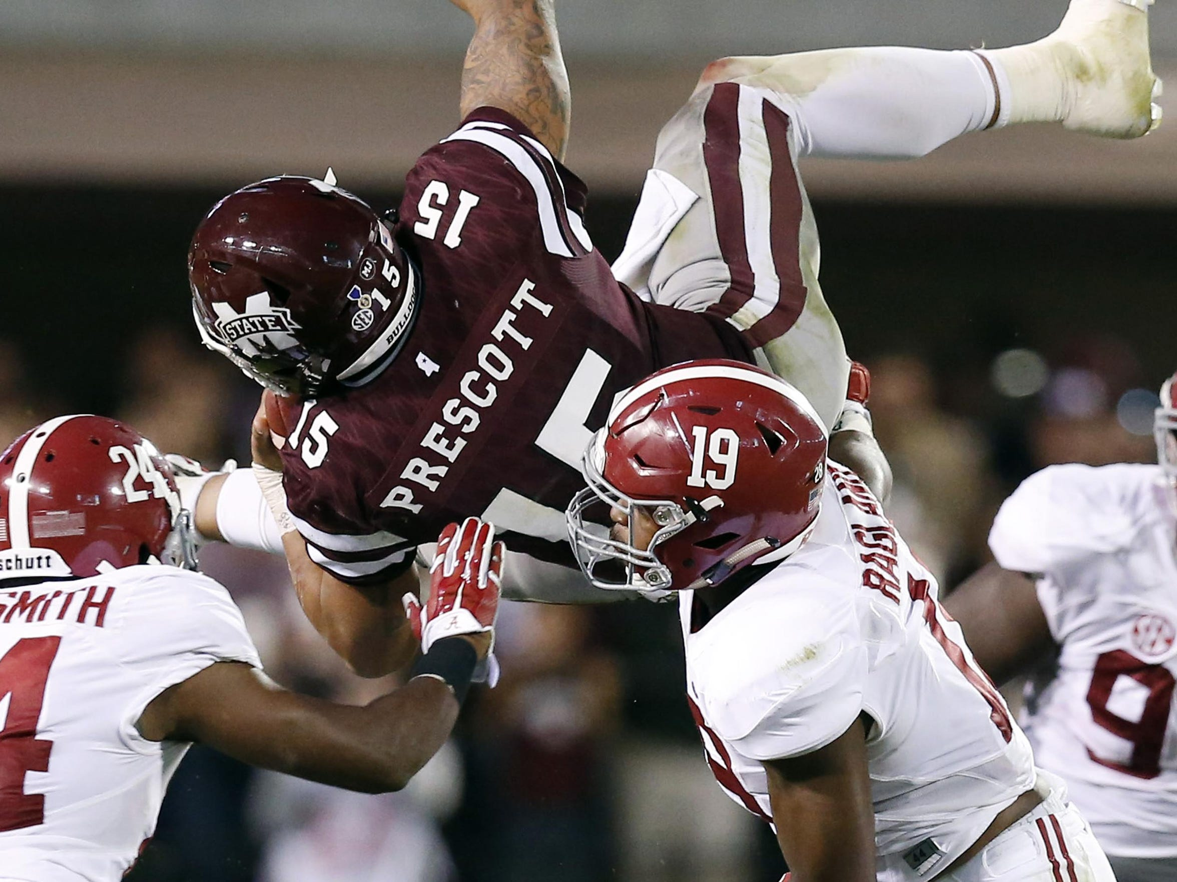 Mississippi State quarterback Dak Prescott is upended by Alabama's defense in Starkville, Miss., on Saturday.