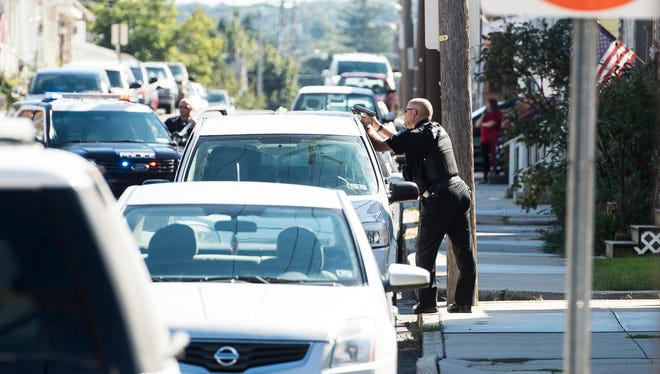 A West Manheim Township police officer takes up a position during a police incident in the 200 block of Locust Street in Hanover Borough on Monday, Oct. 2, 2017.