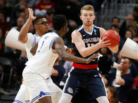 Gonzaga forward Domantas Sabonis, right, looks to pass